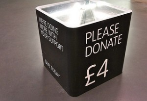 Black donation box, with bold white message: please donate